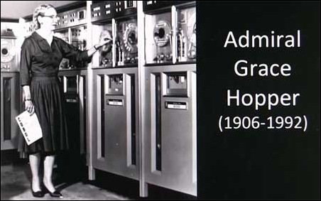 Admiral Grace Hopper standing next to 1950s Univac Computer